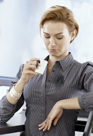 Young businesswoman looking at stain on her blouse made by spilling coffee on it.