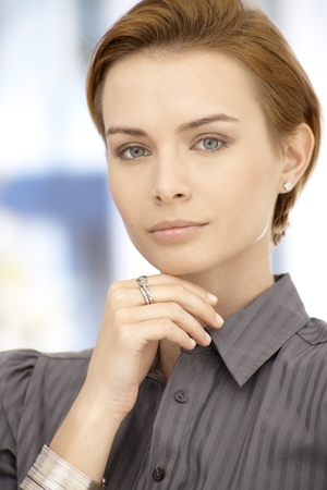 gingerish: Portrait of attractive thinking businesswoman looking at camera, hand on chin.