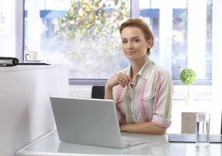 gingerish: Portrait of young woman working in bright office, using laptop computer, looking at camera. Stock Photo