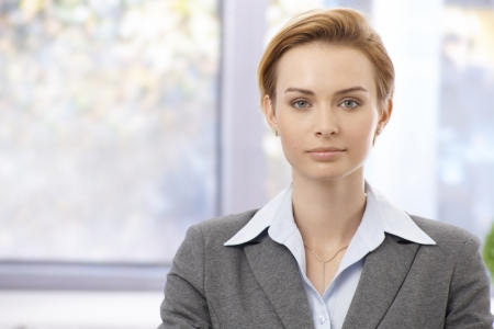 gingerish: Portrait of attractive young elegant businesswoman looking at camera, serious. Stock Photo