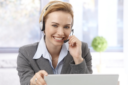 Portrait of beautiful young female dispatcher using headphones, smiling, looking at camera. Stock Photo - 22681799