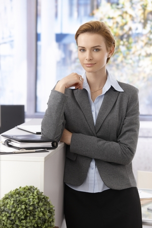 gingerish: Portrait of pretty young businesswoman standing, looking at camera.