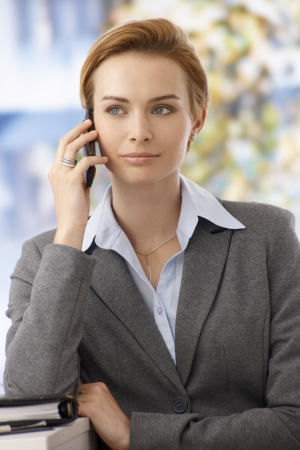 Closeup portrait of beautiful young businesswoman talking on mobilephone, looking away. photo