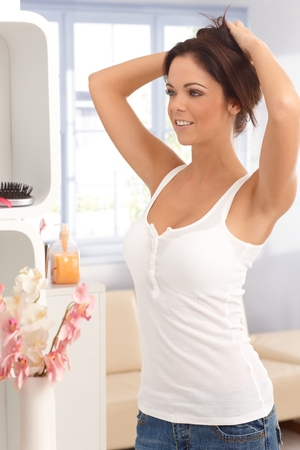 Casual young woman making hair, looking herself in mirror, smiling. photo