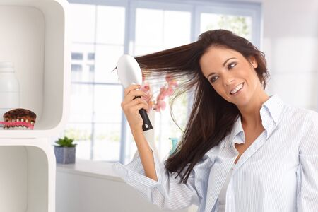 combing hair: Happy young woman combing long hair by hairbrush, smiling. Stock Photo