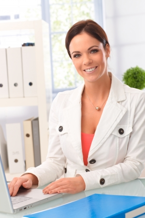 blazer: Happy young woman working in office, using laptop computer, smiling, looking at camera.