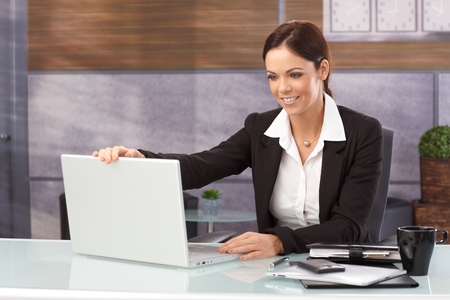 shutting: Happy businesswoman sitting at desk shutting down laptop computer, finishing work.