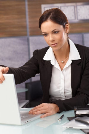 shutting: Tired businesswoman shutting down laptop at the end of the day. Stock Photo