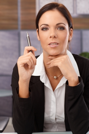 Businesswoman sitting at desk, holding pen, looking at camera. photo