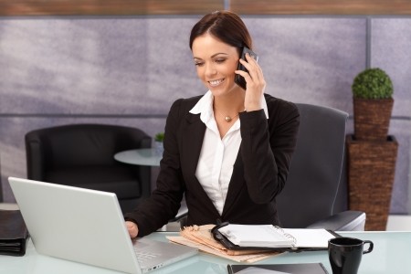 Happy young businesswoman sitting at desk in office, working on laptop computer, talking on mobilephone, smiling. Stock Photo