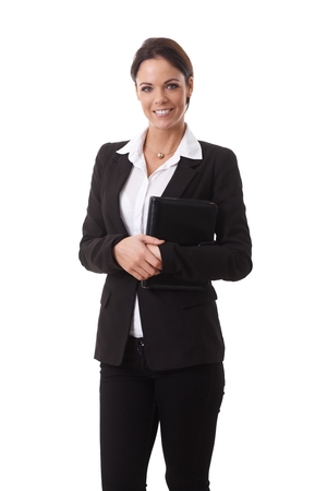 Portrait of happy young businesswoman in black suit, smiling, looking at camera, holding organizer. photo