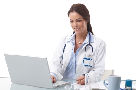 Happy female doctor sitting at desk, working with laptop, smiling. photo