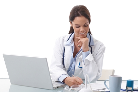 Smiling female doctor doing paperwork, sitting at desk, using laptop. photo