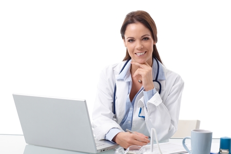 Portrait of happy smiling female doctor sitting at desk, working with laptop, writing.