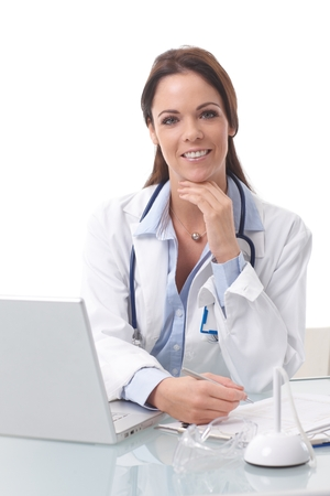 Portrait of young female doctor sitting at desk, working with laptop, smiling, looking at camera. photo