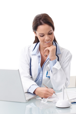 Young female doctor sitting at desk, doing paperwork, using laptop, smiling. photo
