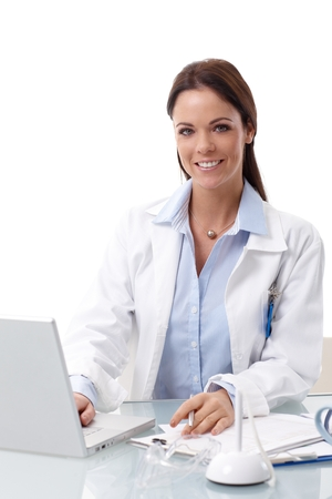 white coats: Happy smiling female doctor sitting at desk, working with laptop, looking at camera. Stock Photo