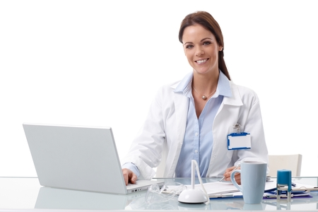 Happy female doctor sitting at desk, working with laptop computer, looking at camera.