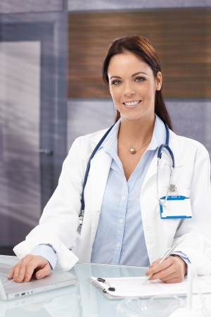 Female doctor working in office, using laptop, smiling, looking at camera. Stock Photo - 22682523