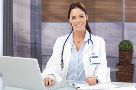 Portrait of attractive young female doctor sitting at desk, working with laptop, smiling, looking at camera. photo