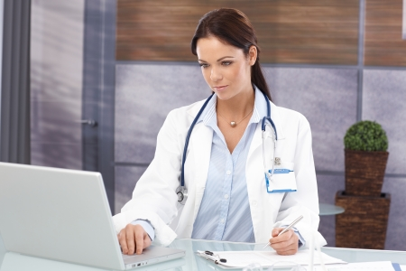 Young female doctor working in office, using laptop computer. photo