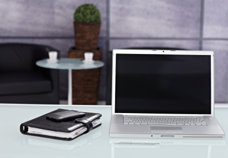 desk tidy: Closeup photo of tidy workplace with laptop, mobile and personal organizer. Stock Photo