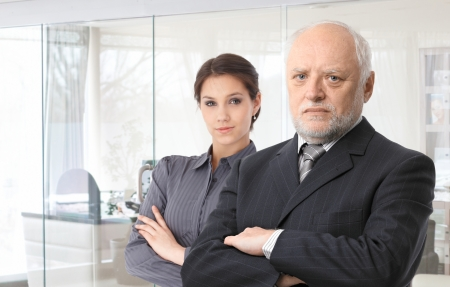 young to old: Portrait of senior male boss and young female secretary standing arms crossed. Stock Photo