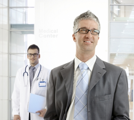 MIddle-aged businessman standing at medical center, smiling, looking away. photo