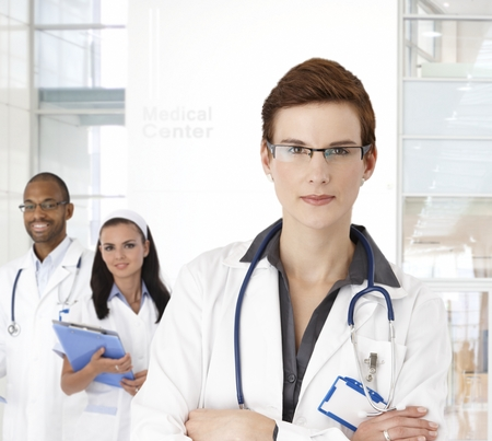 Portrait of young female doctor and team at medical center. Stock Photo