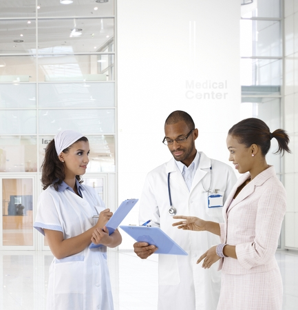 Case discussion at medical center. Doctor, nurse and patient. Stock Photo - 22854289