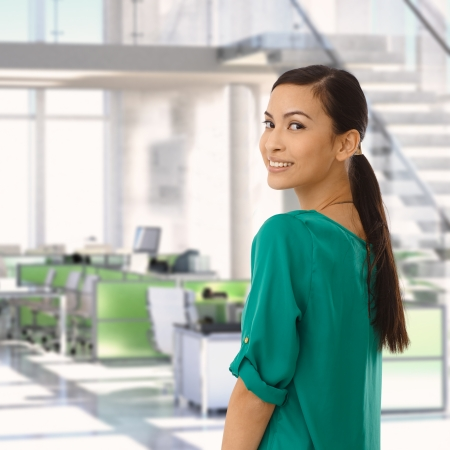 Happy asian businesswoman at office looking back over the shoulder, smiling. photo