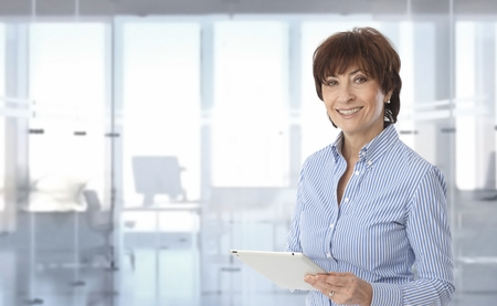 Mid-adult businesswoman using tablet computer at office.