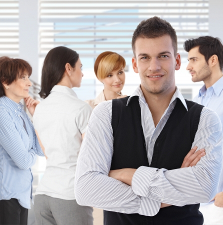 Portrait of young man at office in front of talking business team. photo
