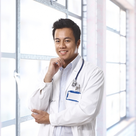 Portrait of happy young asian doctor on hospital corridor, smiling. photo