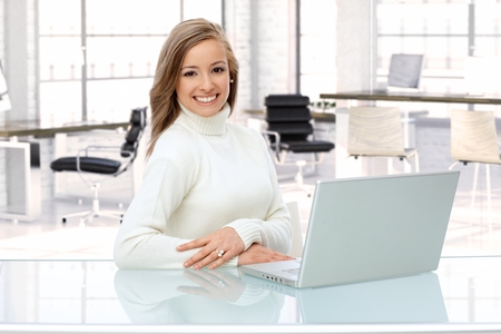 Happy caucasian woman working with laptop at office desk. photo