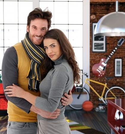Young couple embracing at home, looking at camera smiling. photo