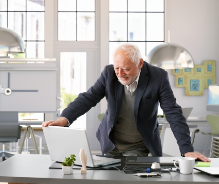 Senior architect standing by desk working with computer at office.