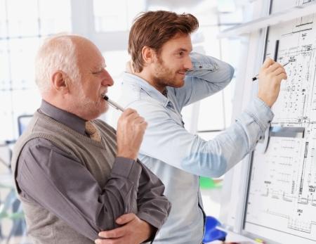 arquitecto: Joven arquitecto trabajando juntos en la tarjeta que siendo supervisado por la alta elaboraci�n.