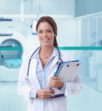 tomograph: Happy female doctor looking at camera in MRI room of hospital.