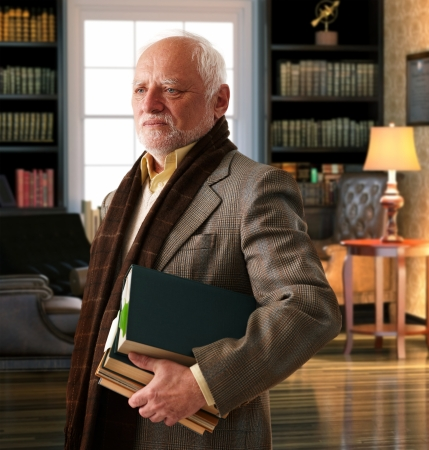 Elderly professor with books leaving library room. photo