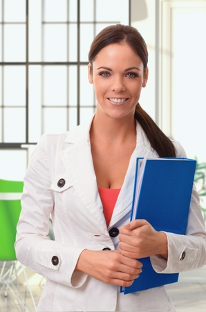 officeworker: Portrait of happy young female officeworker holding folder in colorful setting.