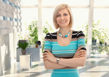 Happy blond female office worker standing arms crossed at office, smiling. photo