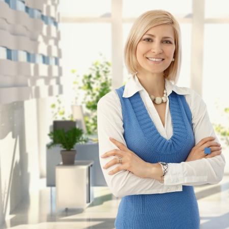 Elegante blonde vrouw in blauwe staande op het kantoor glimlachen naar de camera.