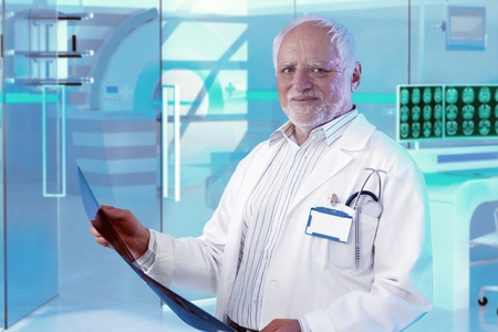 Experienced white-haired male doctor checking MRI scan at hospital photo