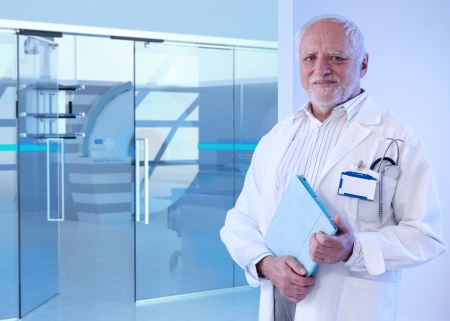 Old doctor standing in front of MRI room at hospital, holding tablet, smiling. photo