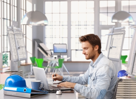 Young architect working at office desk using laptop and digital drawing table. Stock Photo