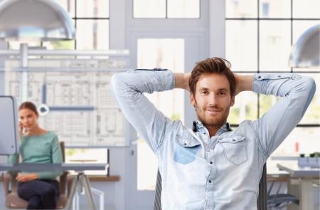 arquitecto: Hombre joven que toma descanso de trabajo en la oficina de arquitecto de moda