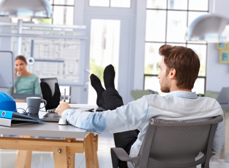 feet up: Architect designing with computer feet up on desk at modern office.