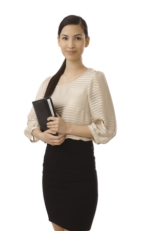 personal assistant: Pretty young businesswoman holding personal organizer, smiling, looking at camera. Stock Photo