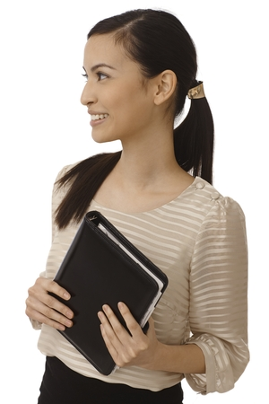pigtails: Attractive Asian businesswoman holding personal organizer, looking right, smiling happy. Stock Photo